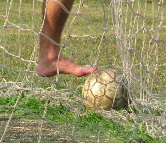 Füße und ein Ball aus Leder. Fußball.