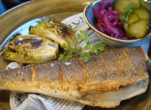 Catch of the Day. Ein ganzer, kopfloser Fisch, gut gegrillt auch die Salatherzen, dazu rote Zwiebeln und Essiggurken. © 2017, Foto: Fritz Hermann Köser, BU: Stefan Pribnow