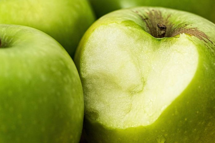 Ein angebissener grüner Apfel.